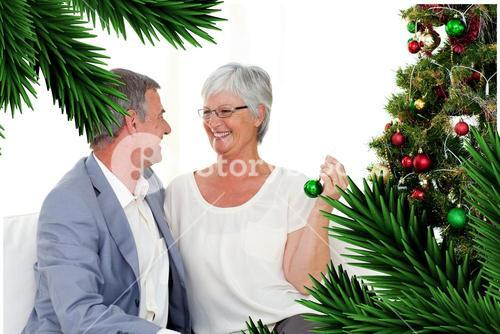 Mature couple sitting on sofa with a christmas tree