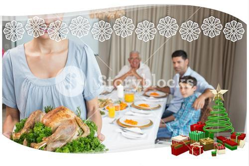 Woman holding chicken roast with family at dining table