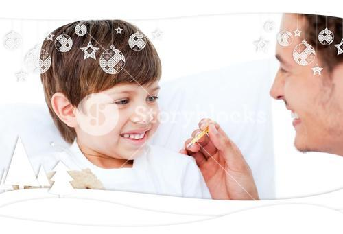 Handsome doctor taking little boys temperature