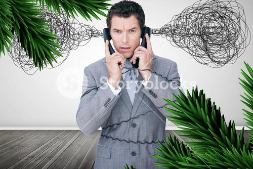 Overworked businessman holding two telephones