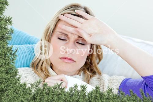 Sick woman with headache lying on the sofa in the livingroom