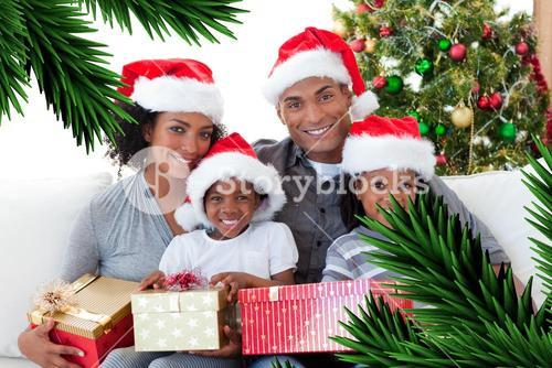 Composite image of family holding christmas presents