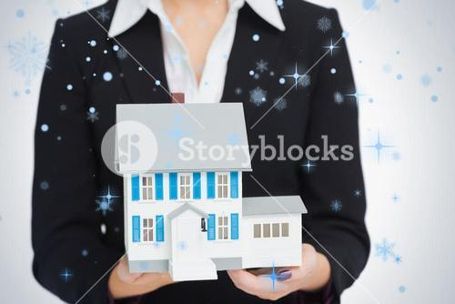 Real estate agent holding a model house
