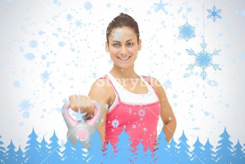 Cheerful sporty brunette holding grey and pink kettlebell