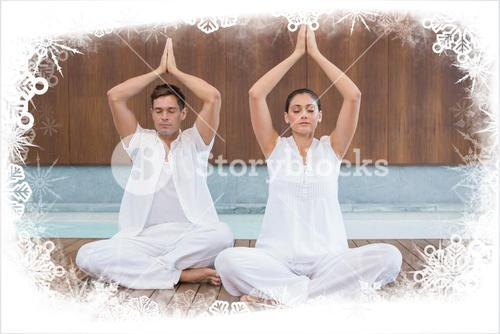 Attractive couple in white sitting in lotus pose with hands together