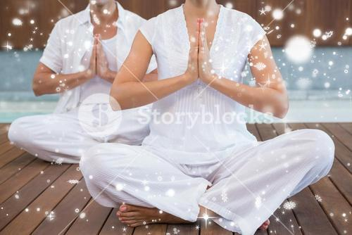 Couple in white sitting in lotus pose with hands together