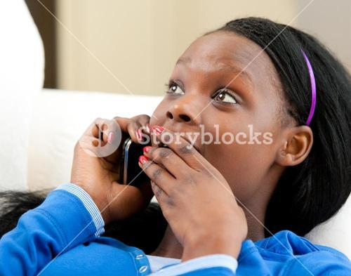 Astonished teenager talking on phone