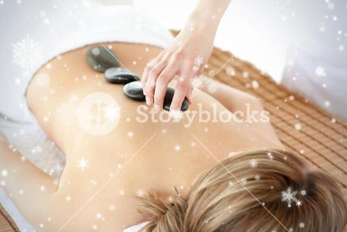 Radiant woman having a stone therapy