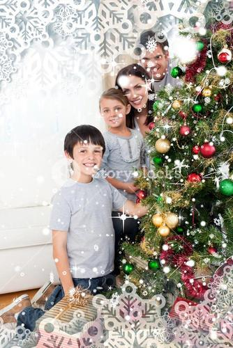 Happy family decorating a christmas tree with boubles and presents