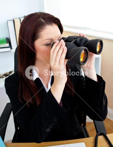 Concentrated businesswoman looking through spyglasses