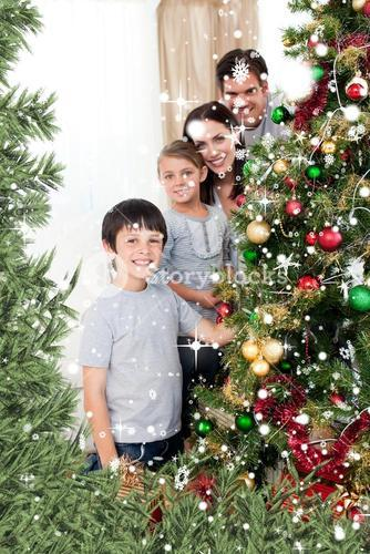 Composite image of happy family decorating a christmas tree with boubles and presents