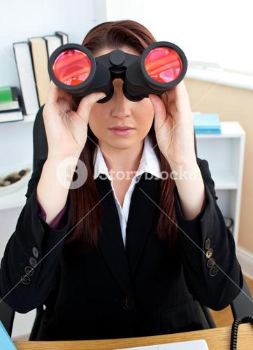 Serious businesswoman looking through spyglasses