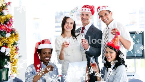 Composite image of smiling business team drinking champagne to celebrate christmas