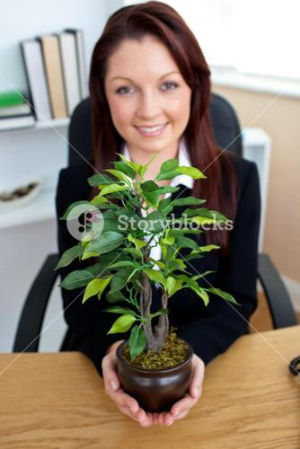 Glowing businesswoman holding a plant