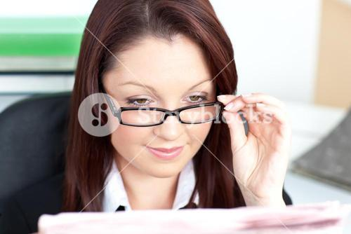 Delighted businesswoman reading a newspaper wearing glasses