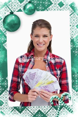 Composite image of portrait of a woman holding bank notes