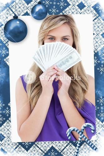 Blonde woman hiding her face behind a fan of notes