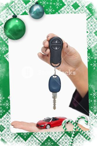 Composite image of woman holding key and small car