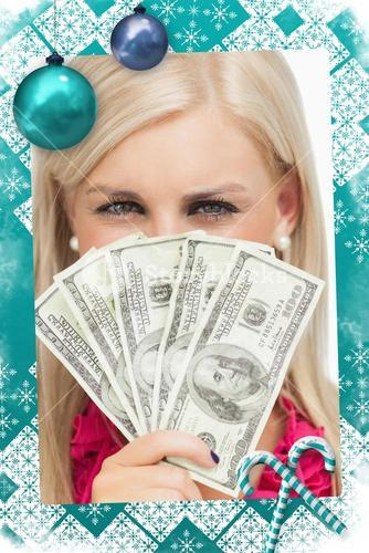 Composite image of blonde hiding her face with dollars banknotes