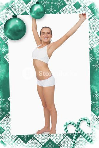 Happy slim woman standing on a scales spreading her arms
