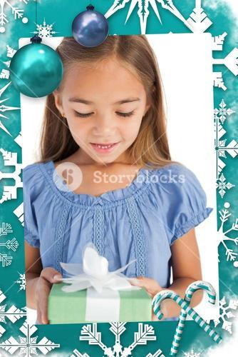 Composite image of cute little girl holding a wrapped gift