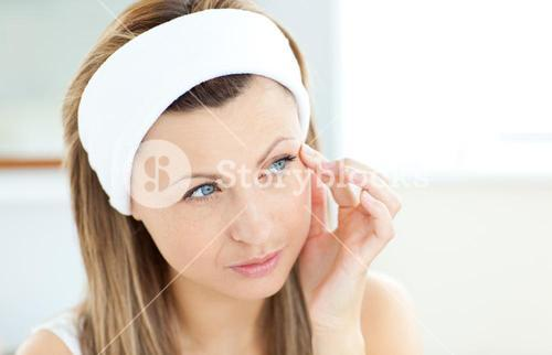 Young woman putting creme on her face