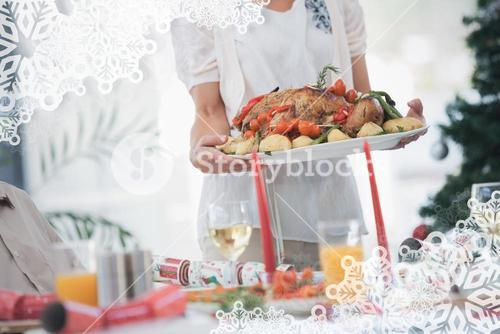 Composite image of woman bringing roast chicken at table