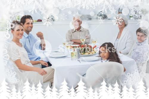 Composite image of family smiling at the dinner table