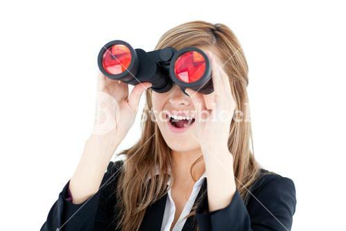 Fascinated young businesswoman looking through a spyglass
