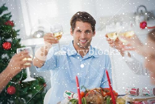 Composite image of family toasting at christmas dinner