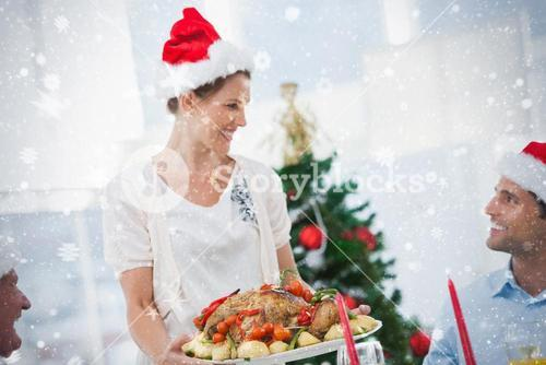Cheerful woman wearing santa hat and bringing a roast chicken