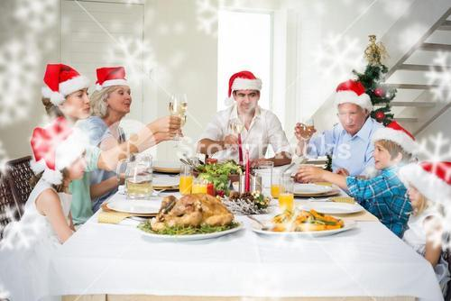 Composite image of family toasting wine while having christmas meal