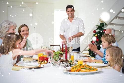 Composite image of family enjoying christmas meal at dining table