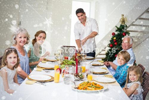 Composite image of family having christmas meal at dining table