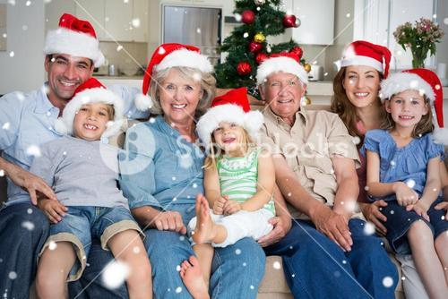 Composite image of family in santa hats celebrating christmas