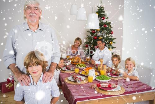 Composite image of grandfather and grandson standing beside the dinner table