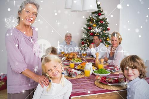 Composite image of grandmother and granddaughter standing beside the dinner table