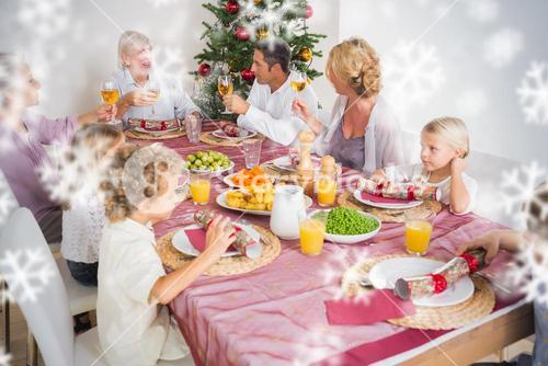 Composite image of adults raising their glasses at christmas dinner
