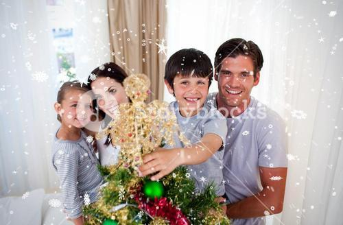 Happy little kid decorating a christmas tree with his family