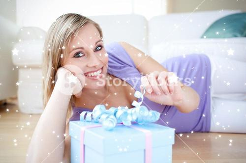 Composite image of delighted blond woman holding a present lying on the floor