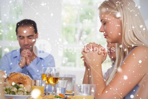 Composite image of woman saying grace with family before dinner
