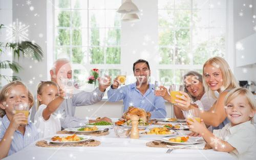 Composite image of happy family toasting at thanksgiving dinner