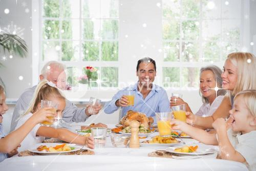 Composite image of family toasting at thanksgiving