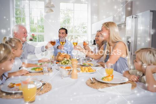 Composite image of adults raising their glasses at thanksgiving dinner