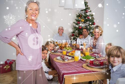 Composite image of grandmother standing beside dinner table