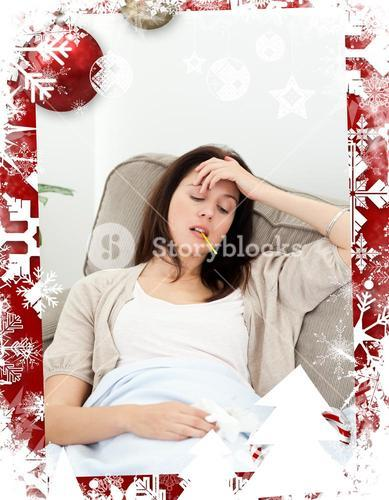 Sick woman taking her temperature with a thermometer on the sofa