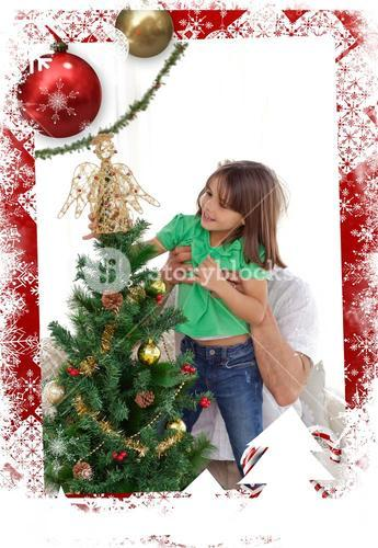 Composite image of attentive father holding her daughter to decorate the christmas tree