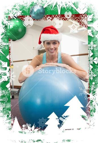 Fit smiling brunette in santa hat leaning on exercise ball