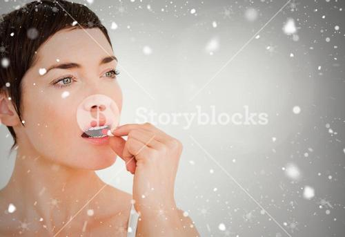 Composite image of close up of a woman taking a pill