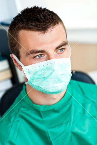 Serious male surgeon with mask and scrubs
